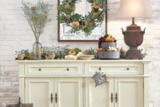 21 a harvest-themed console table with faux pumpkins, greenery, pinecones, faux fruit on a metal stand