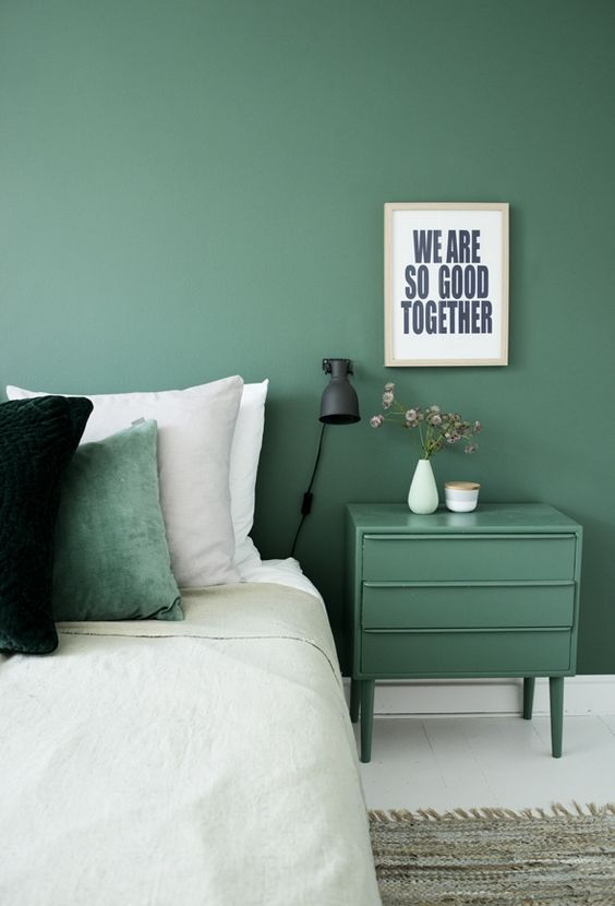 a muted green wall and a matching nightstand plus a matching pillow for relaxation and comfort