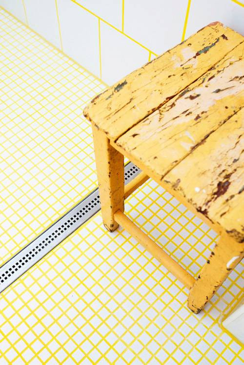 little white tiles and large ones are tied with each other usign bright yellow grout plus a yellow stool that echoes with it