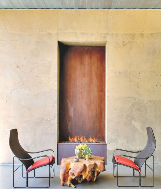a luxurious fire pit space with a unique coffee table and creative bold chairs