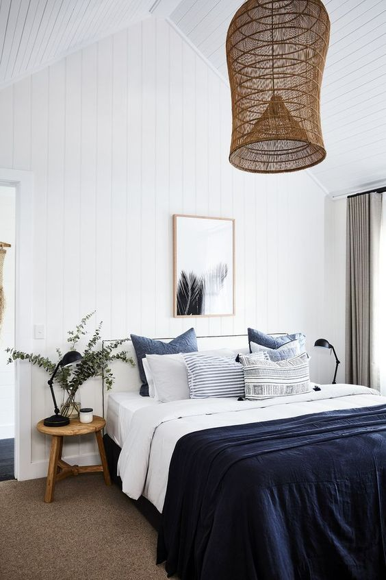 a navy blanket and pillows for adding a touch of color to the neutral space