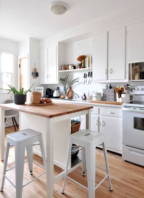 a small white kitchen island with storage shelves and a meal zone with stools
