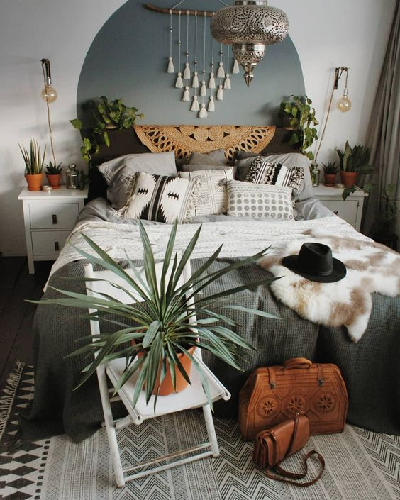 a tassel hanging, potted greenery, faux fur, a jute rug and a silver lamp in Moroccan style