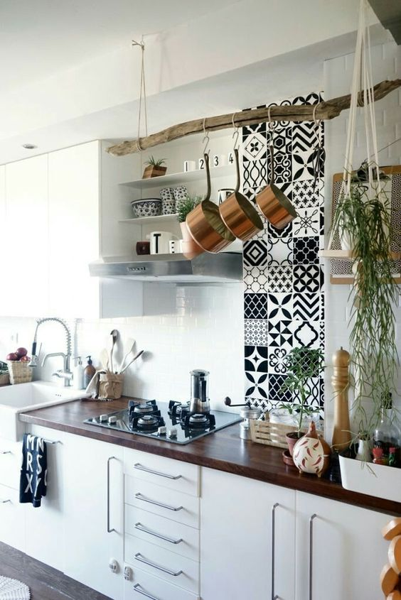 a vertical mosaic tile feature, a tree branch pot holder and cascading greenery in a hanging planter for a boho feel