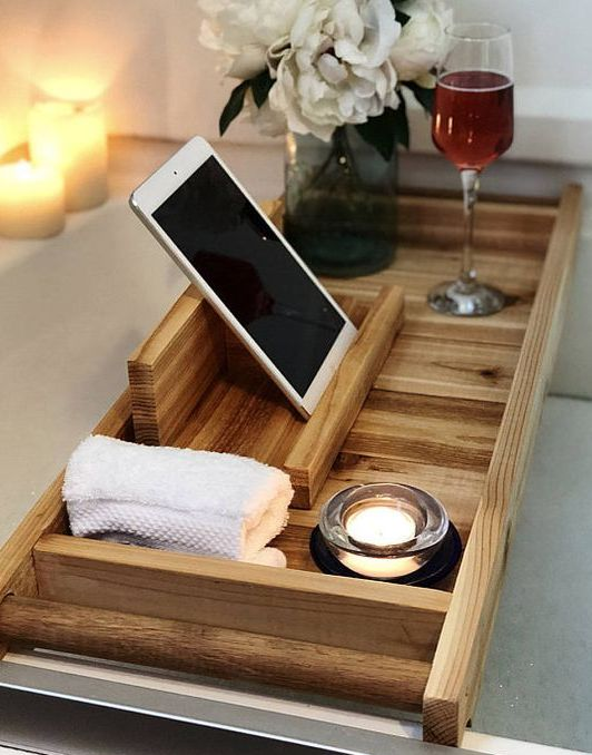 a wooden bath tray with comfy handles and a large gadget or book holder is a very functional piece