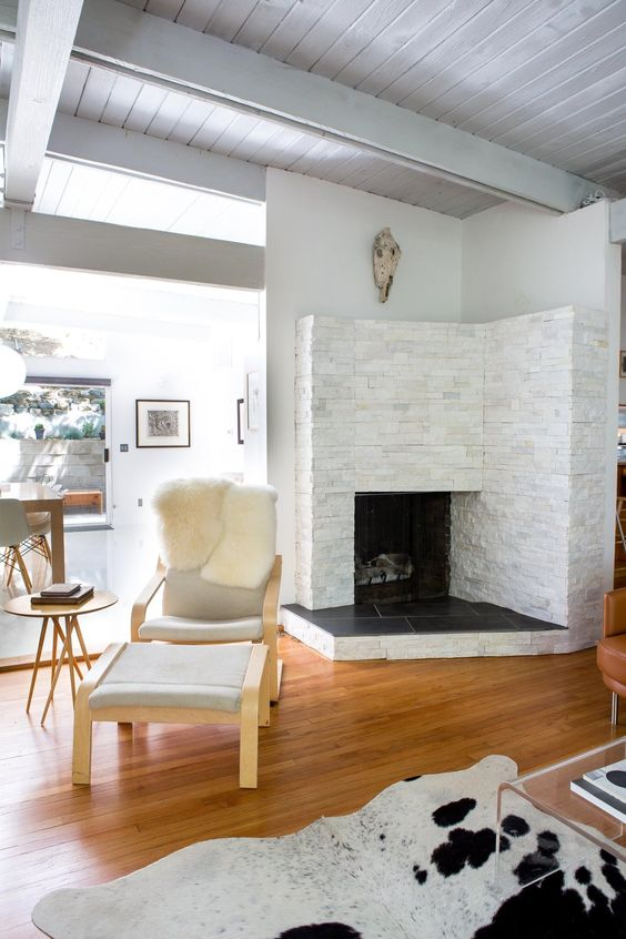 a cozy fireplace nook with a leather chair and a footrest plus a cowhide rug for reading