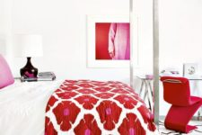 23 a luxurious white bedroom with a hot red chair, artwork and a floral bedspread