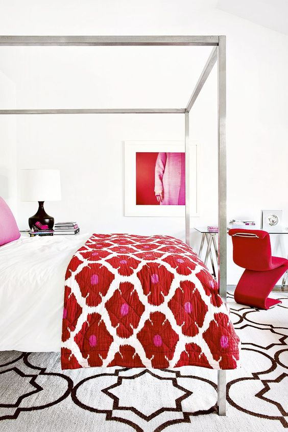 a luxurious white bedroom with a hot red chair, artwork and a floral bedspread
