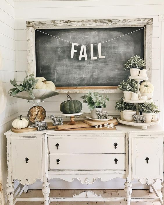 a vintage carved console table with white and grene pumpkins, greenery in pots and vintage figurines