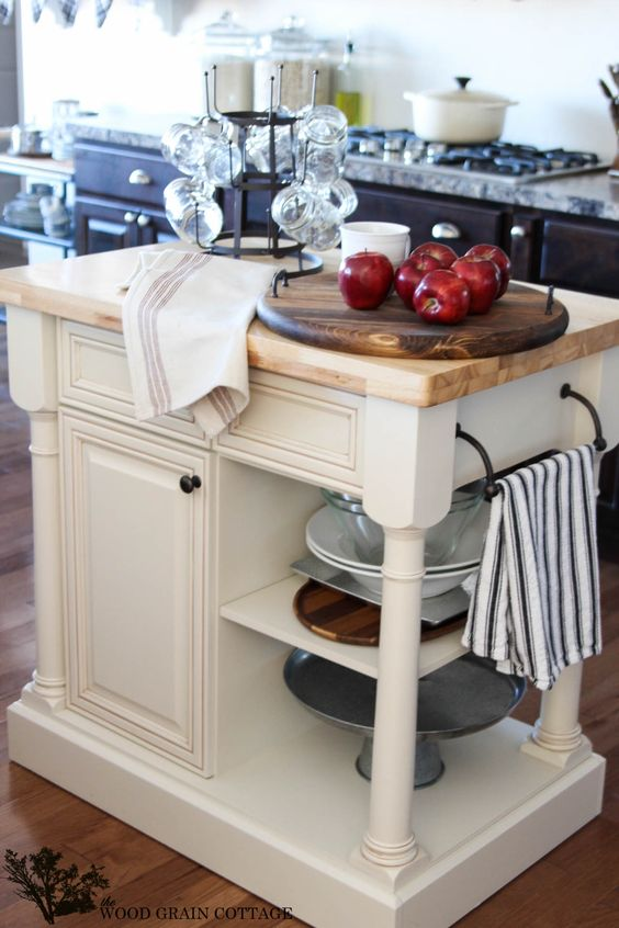 a vintage rustic kitchen island in white with much storage space and a wooden countertop