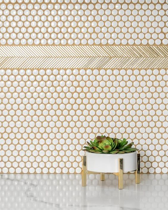 white penny tiles spruced up with gold grout and a planter on gold legs for an accent