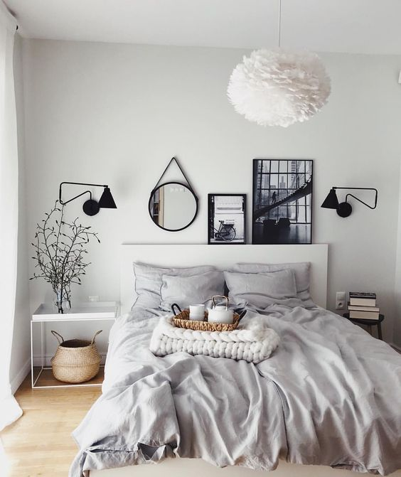a light grey bedroom enlivened with some artworks, a mirror and sconces in black for depth