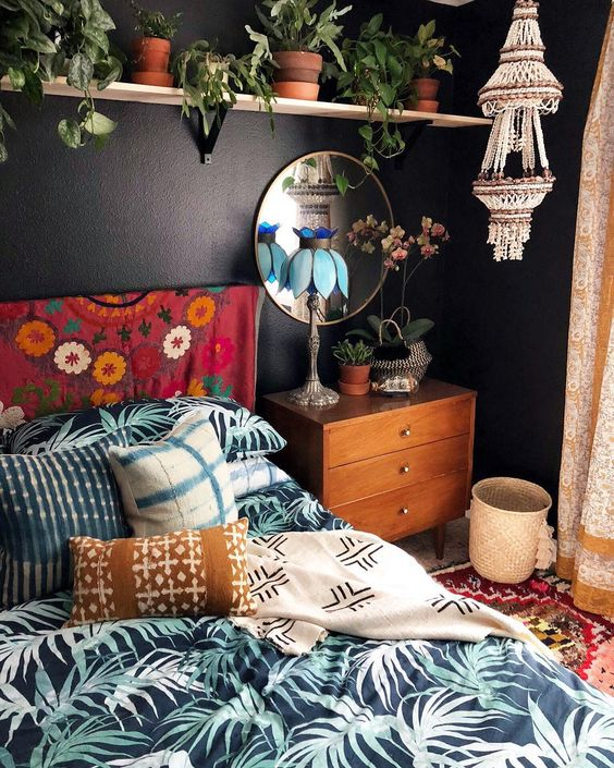a macrame and bead chandelier, printed textiles and a lot of potted greenery make the space boho