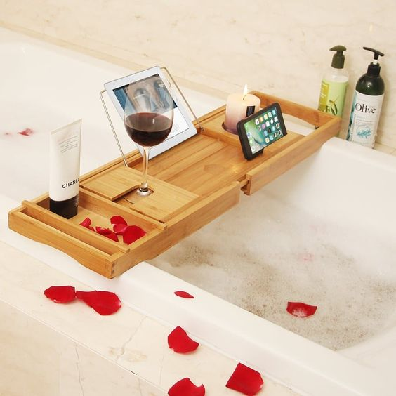 a modern bathroom caddy with a wine glass holder, a candle holder and a gadget stand