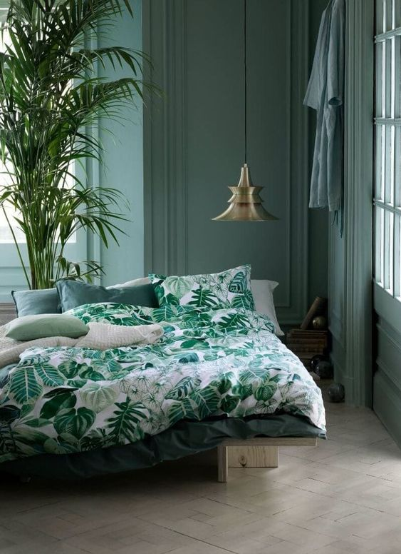 a muted green bedroom and a bright green bedding set with a botanical print for maximal relaxation