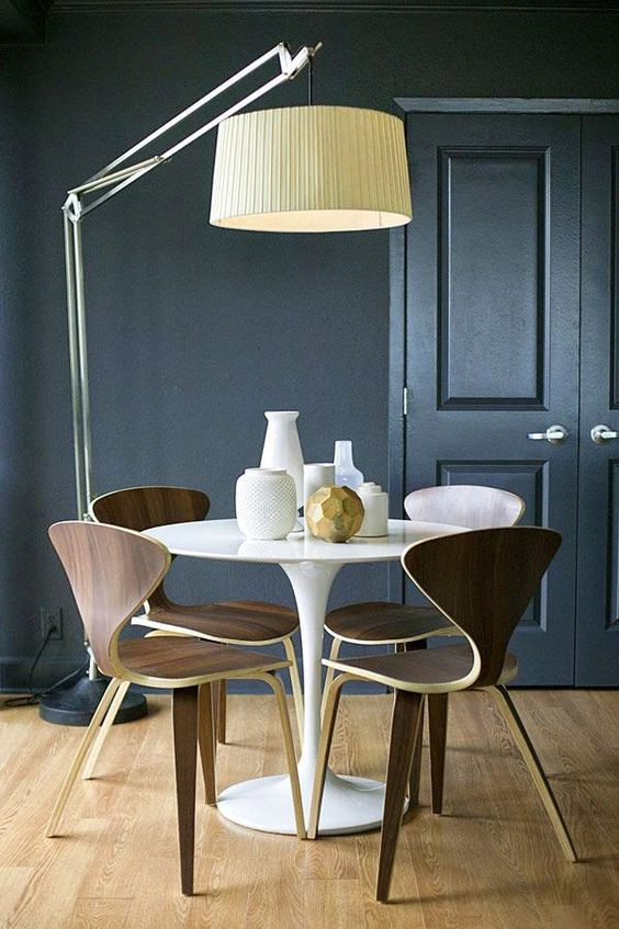 a statement flooor lamp with a metal leg and a large faric lampshade to accent the table