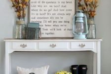 24 a vintage console with dried blooms and herbs, a lantern and a natural pumpkin on the floor