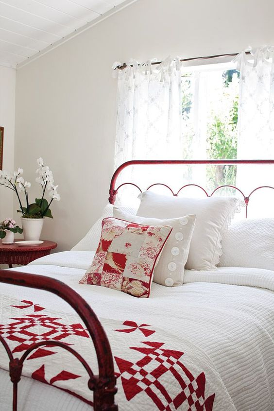 a white bedroom with a red metal frame bed and a matching wicker nightstand