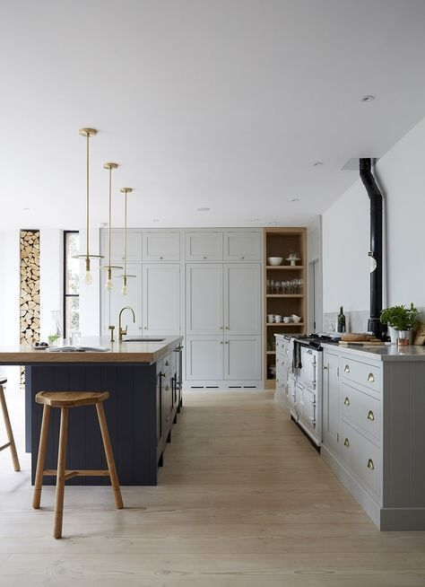 vintage-inspired grey cabinets and a navy kitchen island in the same style with a wooden countertop for a chic look