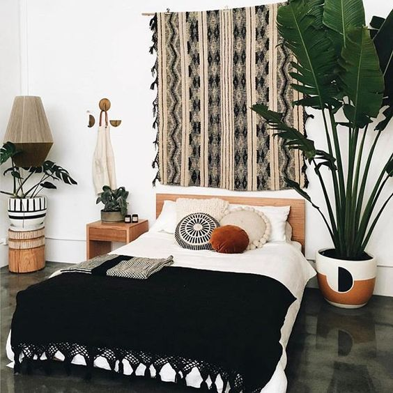 a boho textile artwork, a black tassel bedspread, potted greenery for creating a bold boho look