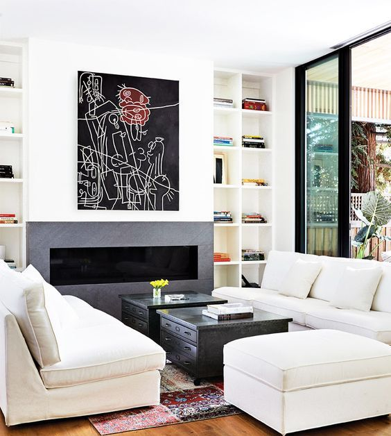 a modern built in fireplace with comfy white upholstered furniture and a couple of coffee tables