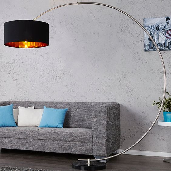 a statement floor lamp with a base on the floor and a rounded long 'leg' and a large black and metallic lampshade