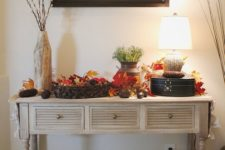 25 a vintage rustic console table with baskets, fall leaves, pinecones, corn cobs and greenery in a vase