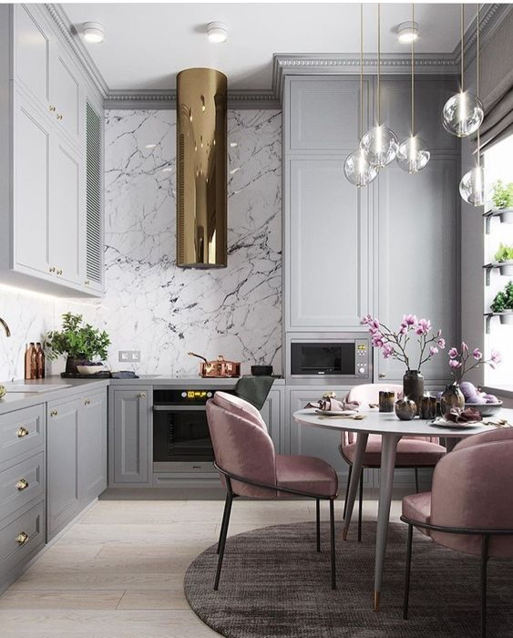 pale pink chairs add color to the monochromatic kitchen with metallic touches