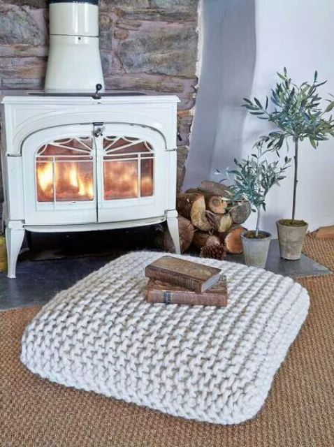 a traditional space by a large hearth with a rug and a chunky knit cushion on the floor