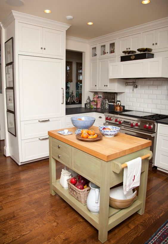 an olive green kitchen island with a wooden countertop, drawers and open storage in rustic style