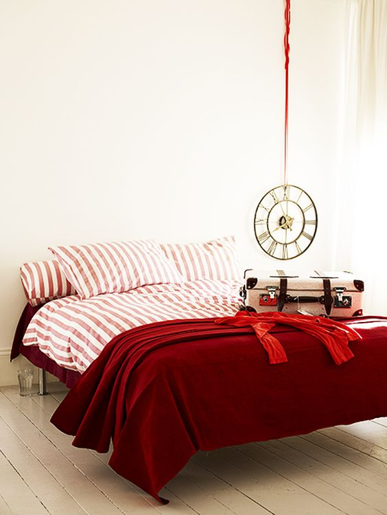 deep red and pink and white striped bedding set spruces up a neutral bedroom and raises the mood