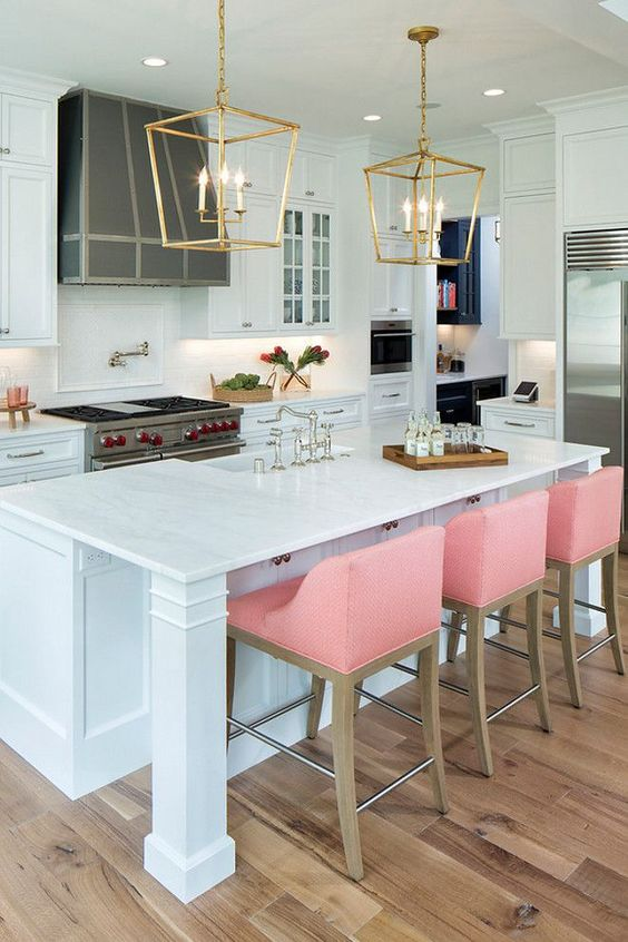 pink stools add color to the traditional kitchen in white and create a modern twist
