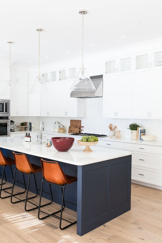 white cabinets with a navy kitchen island and a white countertop that echoes with the cabinets themselves