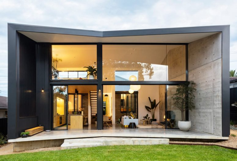This cool pavilion like home addition is an amazing contemporary space with a glazed wall that opens it up to the backyard