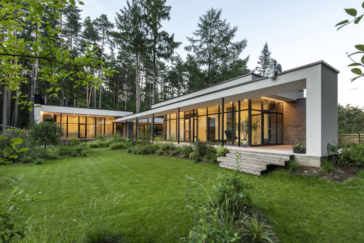 This stylish ontemporary home is located on a forested site and some pines are growing through