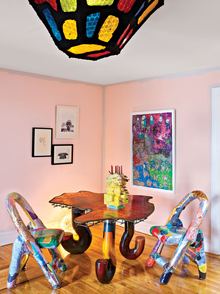 The dining room is super colorful, with bold chairs, an artwork, a pendant lamp and look at these table legs