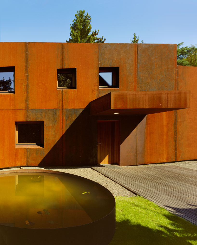 The house is clad with rust colored metal, which is highlighted with naturally neutral surroundings