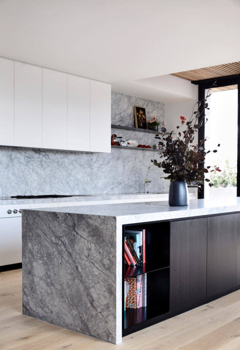 The kitchen features white cabinets, stone surfaces and a dark kitchen island