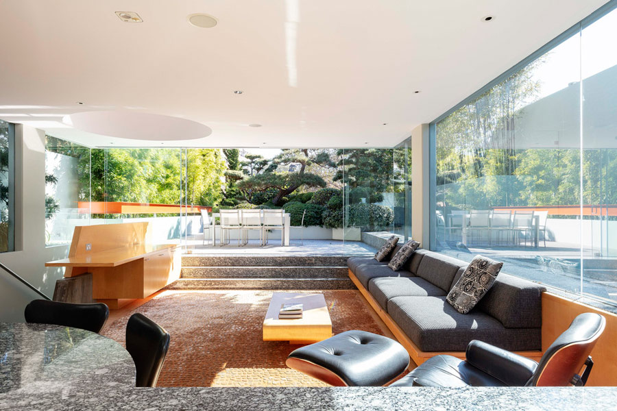The living room and kitchen are united into an open layout with glazed walls, they are sunken to make the furniture built in