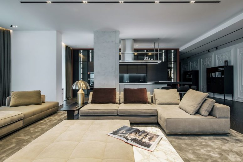The living room, dining space and kitchen are united into one open layout, and the living space is marked with a large rug