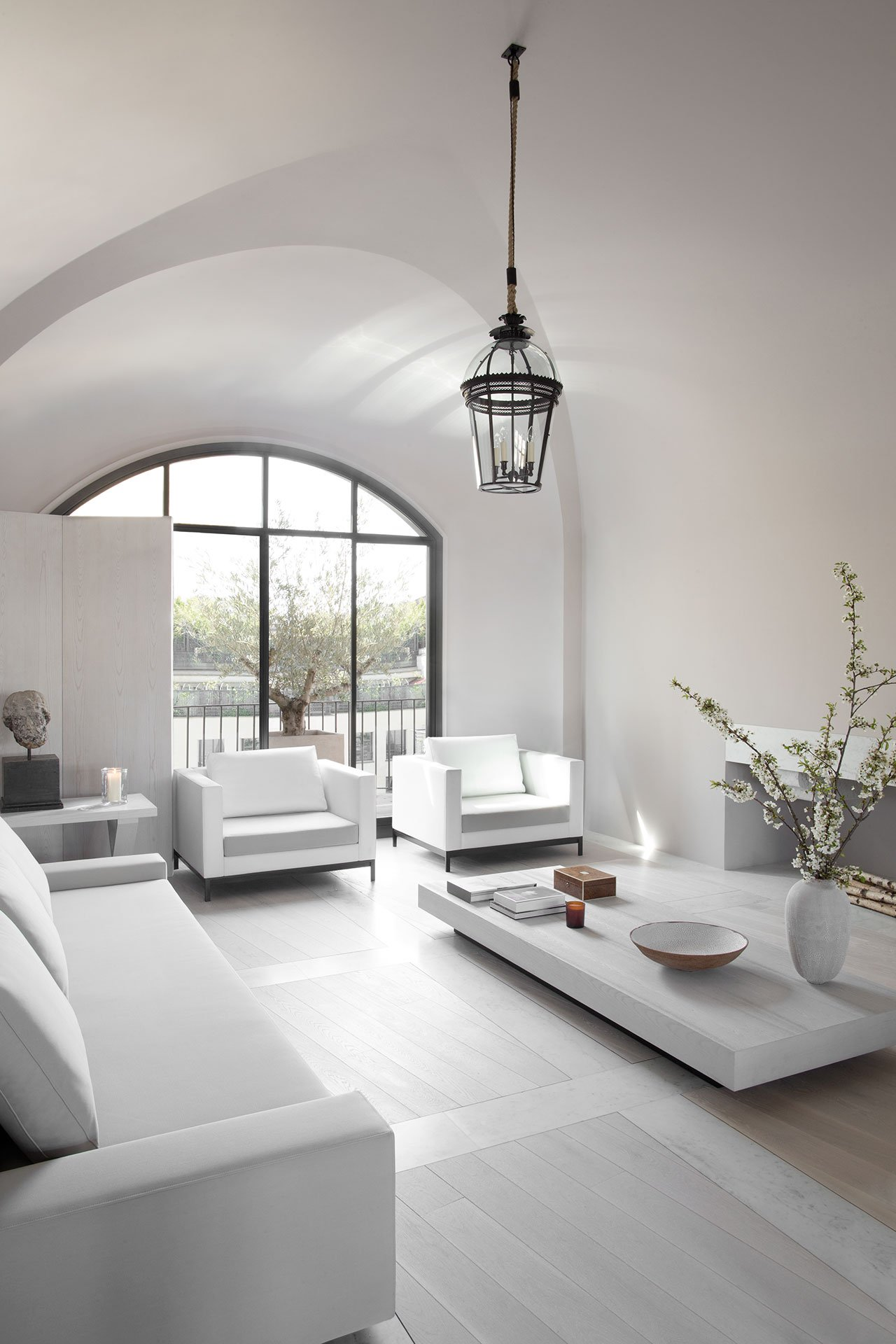 The living room is a light filled space with white furniture and much light coming through an arched window