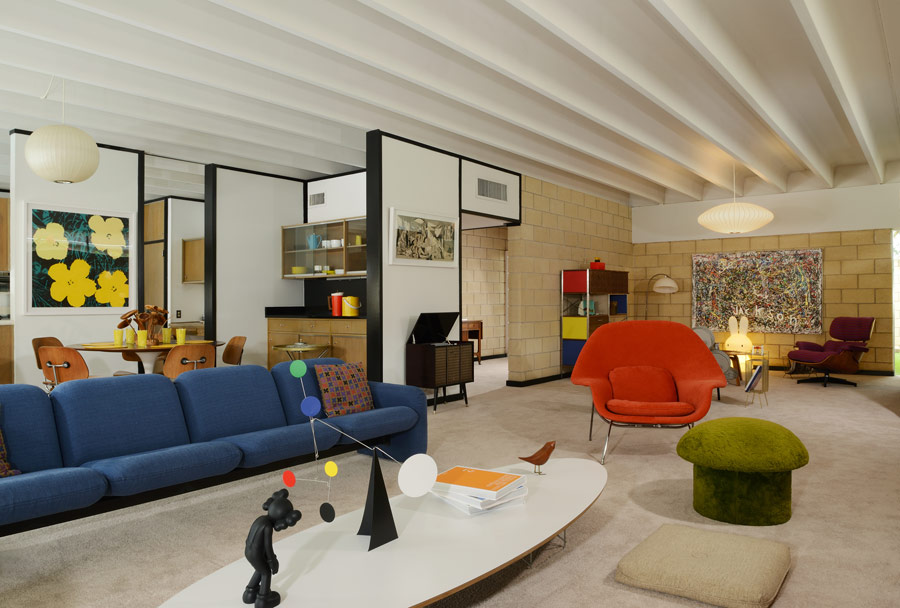 The living space is a open layout with bright furniture and accessories and comfy sitting spaces