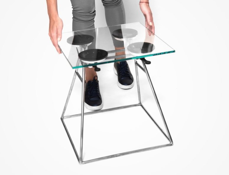 The stool features a metal base, some suction cups and a glass top or seat