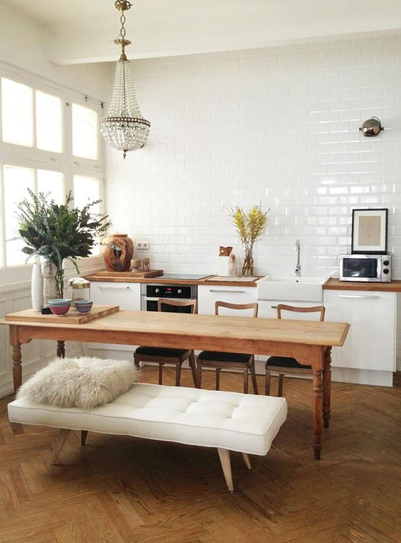 a chic eclectic space with a vintage wooden table and kitchen island and an upholstered bench for an accent