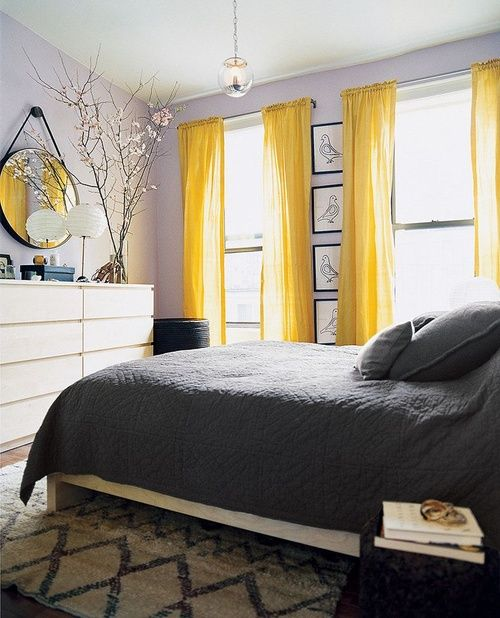 a lavender space with greys and neutrals and yellow curtains that add color and a cheerful feel