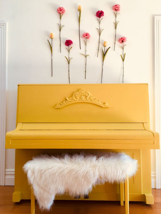 a yellow piano with a faux fur stool and faux blooms attached to the wall for a feminine feeling