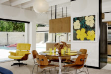03 The dining space is done with a round table and chairs and a bright artwork and is separated with a narrow wall