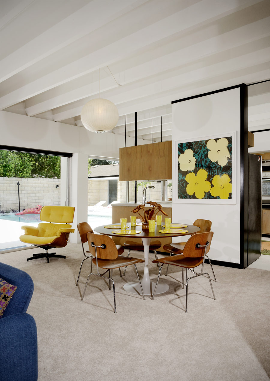 The dining space is done with a round table and chairs and a bright artwork and is separated with a narrow wall
