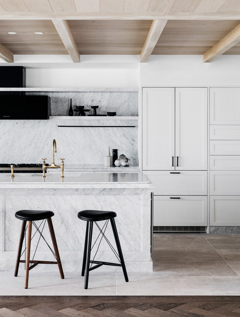 The kitchen is done with white cabinets, white marble and black touches for a dramatic feel