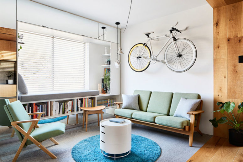 The living room shows off a bike on the wall, some built-in shelves and comfy furniture